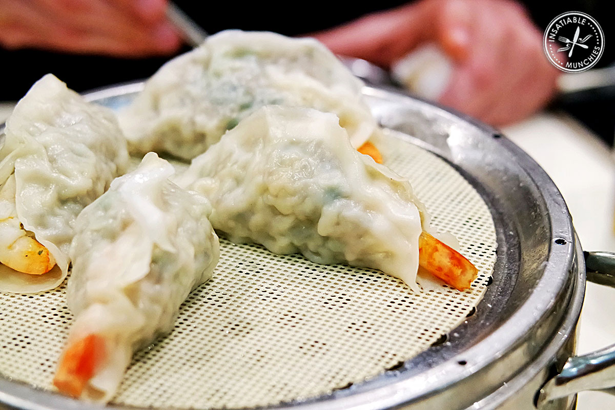 A mixture of pork, sweet potato noodles, and salted cabbage is wrapped into a dumpling with a whole prawn, and steamed in a metal steamer.