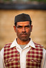 Indian man in chequered waistcoat and black hat