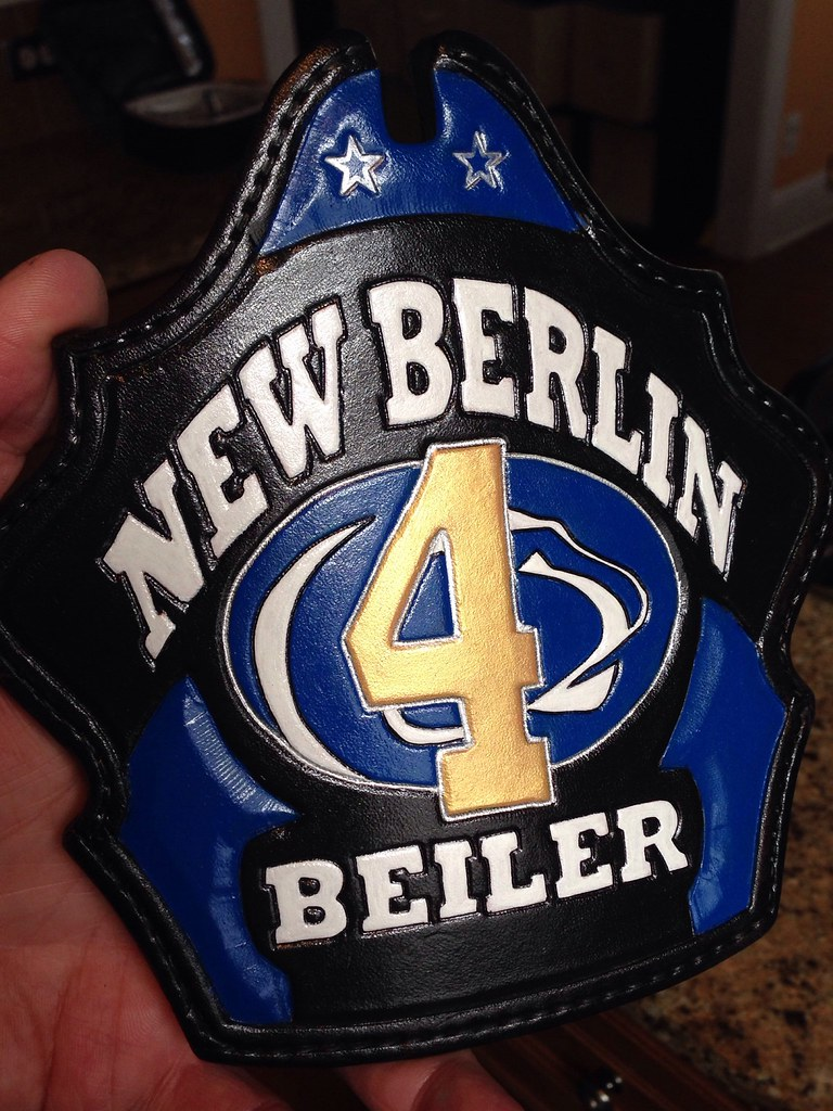 Custom fire helmet shield with gold number and Penn State logo.
