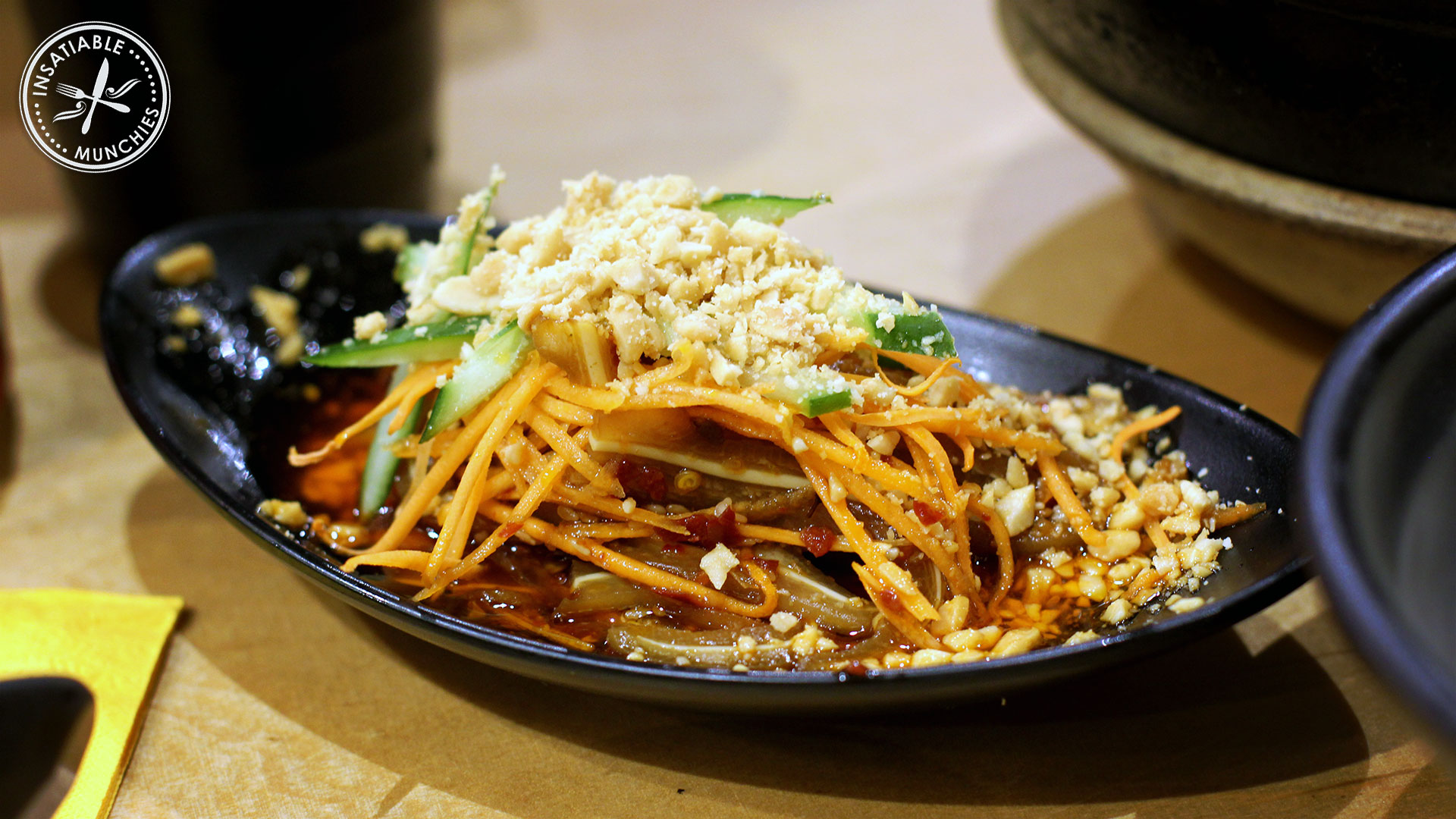 Pig's ears, cooked and finely sliced. Mixed with chilli oil, peanuts, finely sliced carrots and cucumbers, and sze chuan peppers.