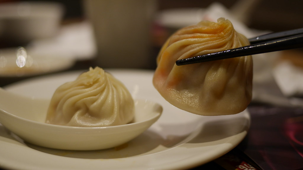 Chili-crab xiaolongbao (between chopsticks) is indeed larger than signature pork xiaolongbao (on spoon)