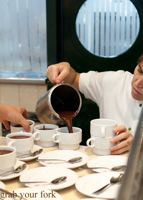 Pouring luscious thick Spanish hot chocolate into cups at Chocolateria San Gines in Madrid, Spain