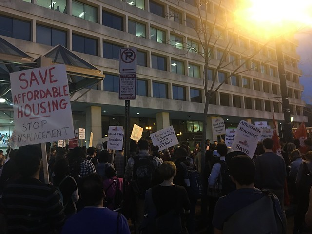 A crowd gathered in front of the Wilson building. A sign is held high that reads,