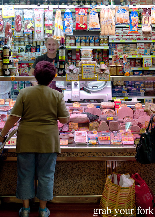 Delicatessen worker and customer in Mercado de la Cebada in Madrid, Spain