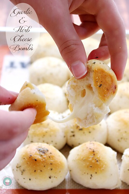 Garlic & Herb Cheese Bombs being torn a part with the cheese stretching between the two pieces.