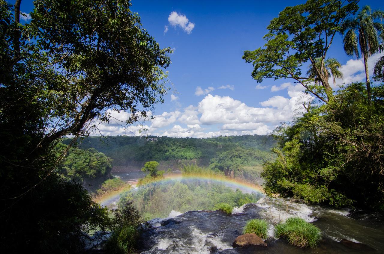 Postal de la vasta naturaleza y el brillo del arcoiris a medida que se avanza por el sendero sobre la superficie del río Iguazú hacia las cataratas. (Elton Núñez).