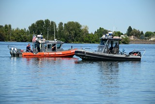 Coast Guard crew members aboard a 25-foot Response Boat  Small talk with Benton County Sheriff deputies as together they patrol the northern safety zone line where boaters could anchor their vessels while watching the annual boat races held on the Columbia River near Kennewick, Wash., July 25, 2014.  . . The boat races, and accompanying air show, is a big event for the Tri-Cities area with hundreds of people on shore and on the water gathering together to enjoy the festive weekend. (U.S. Coast Guard photo by Petty Officer 1st Class David Mosley)