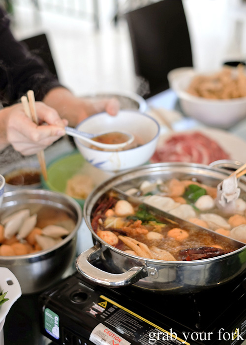 Dipping meat and scooping soup during steamboat hot pot