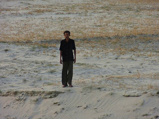 Iqbal stands in the middle of a plain where his village once was