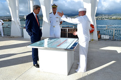 A Navy seaman briefs U.S. Secretary of State John Kerry and U.S. Navy Admiral Samuel Locklear, commander of the U.S. Pacific Command, on the attack that sank the USS Arizona in Pearl Harbor, Hawaii, drawing the United States into World War II, on August 13, 2014, after the two laid a wreath at the famed site. It followed a regional military briefing coming at the conclusion of an around the world trip that included stops in Burma, Australia, and the Solomon Islands. [State Department photo/ Public Domain]