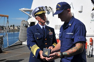 Coast Guard Commandant, Adm. Paul Zukunft, recognizes Petty Officer 2nd Class Matthew Baasch from Coast Guard Cutter Bertholf in Alameda, Calif., Sept. 16, 2014, for his role in two separate counter narcotics off the coast of Colombia. The crew of Cutter Bertholf recently returned from a 140-day patrol off the coast of South America. (U.S. Coast Guard photo by Petty Officer 2nd Class Patrick Kelley)