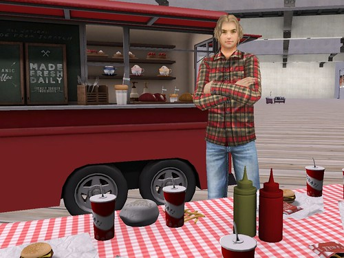 Image Description: Man standing in front of a food truck and behind a picnic table.