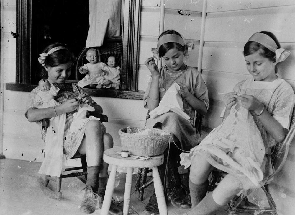 Three sisters doing needlework on the verandah of their Toowong home ca. 1918