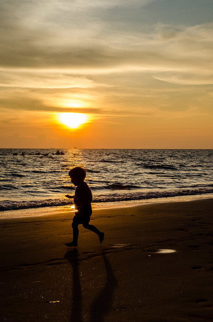 Happy kid running on beach at Pantai Morib, Tanjung Sepat