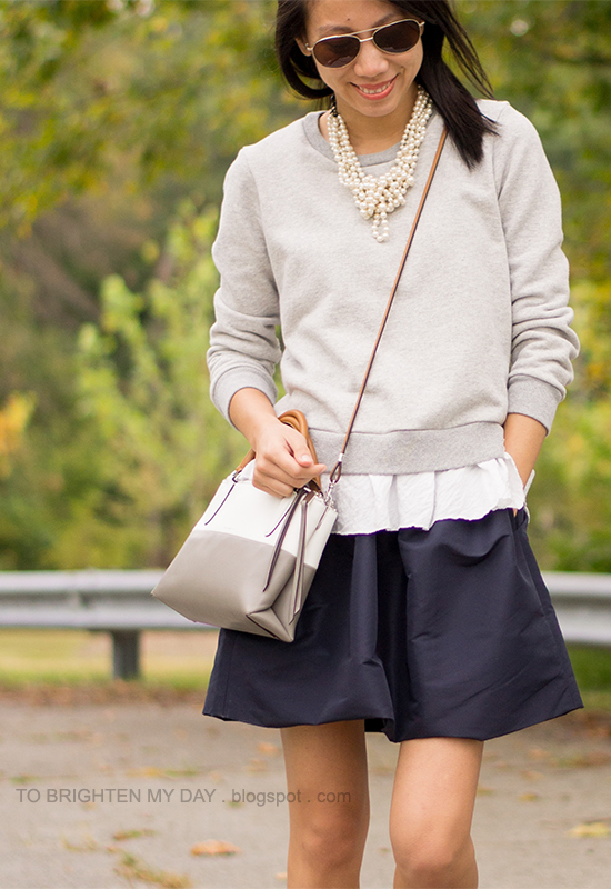 wrapped pearl necklace, ruffled sweatshirt, navy skirt, crossbody colorblocked bag
