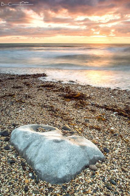 gravel rock sunrise sea waves long exposure