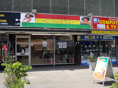 "A fully-glazed shopfront with a sign above showing two brown-skinned people with fancy hair.  The rest of the sign consists of red, yellow, and green stripes (as in the national flag of Ghana, though without the black star) and the words ""Adom Unisex Salon & Hair Products"" along with details of opening hours."