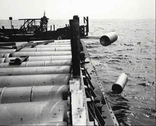 1964年,一台起重機剷起一噸鐵桶-裡面裝有芥子氣-從船上扔進大西洋,而接下來數十年間,軍方就用這種方式將數百萬磅的化學戰劑扔入海裡。U.S. Army photos, Daily Press / September 19, 2005