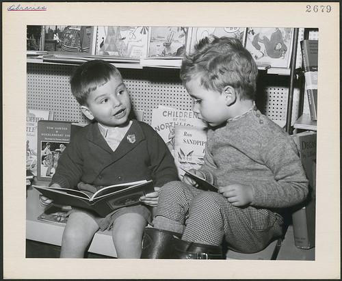 Two young boys, seated with books, in the children's department of a Toronto public library, Toronto, Ontario / Deux jeunes garçons lisent dans la section pour les enfants d'une bibliothèque publique de Toronto (Ontario)