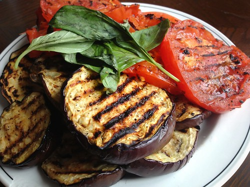 grilled aubergines and tomatoes with basil leaves