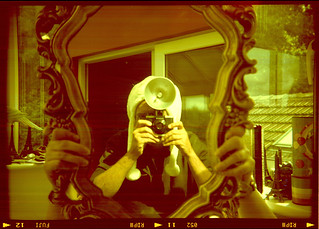 reflected self-portrait with Ansco Readyflash camera and furry white hat