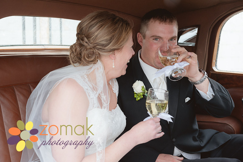 bride and groom toast and laugh with champagne in an antique rolls royce