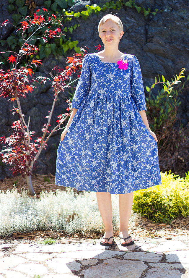tea-length floral blue dress and hot pink hibiscus brooch