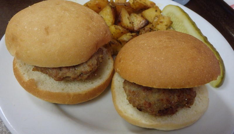 two hamloaf sandwiches with fried potatoes and a pickle