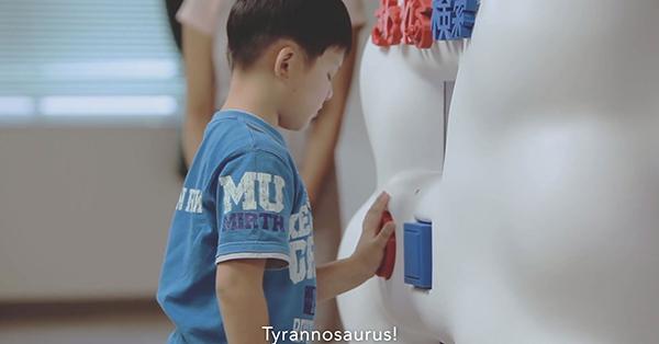 한 남자아이가 기계 앞에 서서 '공룡'이라고 말한다. 기계는 '공룡'이라는 단어에 해당하는 3D 도면을 데이터베이스에서 찾는다.