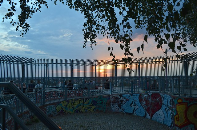 Berlin Park Volkspark Humboldthain bunker platform with graffiti and iron fence framing sunset