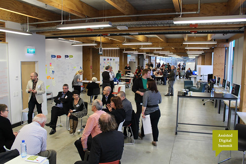 A photo showing groups different groups of people in an open plan industrial-designed workspace.