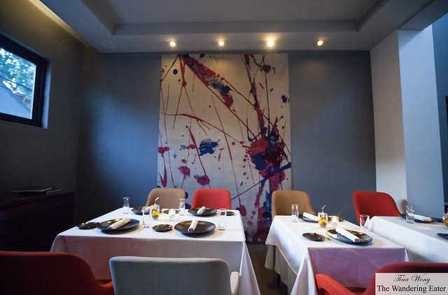 Another dining area with a large modern painting to match the colors of the seating