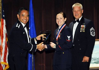Coast Guard Petty Officer 3rd Class Whitney Jackson, a maritime enforcement specialist assigned to Coast Guard Maritime Force Protection Unit Bangor in Silverdale, Wash., accepts the Julius A. Kolb Airman Leadership School Commandant's Award from Air Force Col. David Kumashiro (left), commander of the 62nd Airlift Wing at Joint Base Lewis-McChord, Wash., and Air Force Command Chief Master Sgt. Gordon Drake, command chief of the 62nd Airlift Wing, during the graduation ceremony for ALS class 14-E at JBLM, July 10, 2014. Jackson was nominated by her fellow classmates and school instructors for the award because of her leadership skills.
