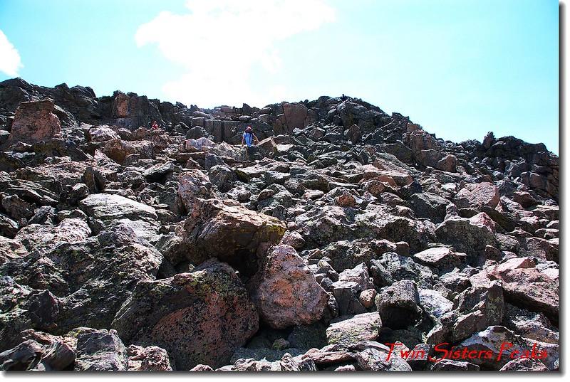 登山客正在岩石坡攀登東峰