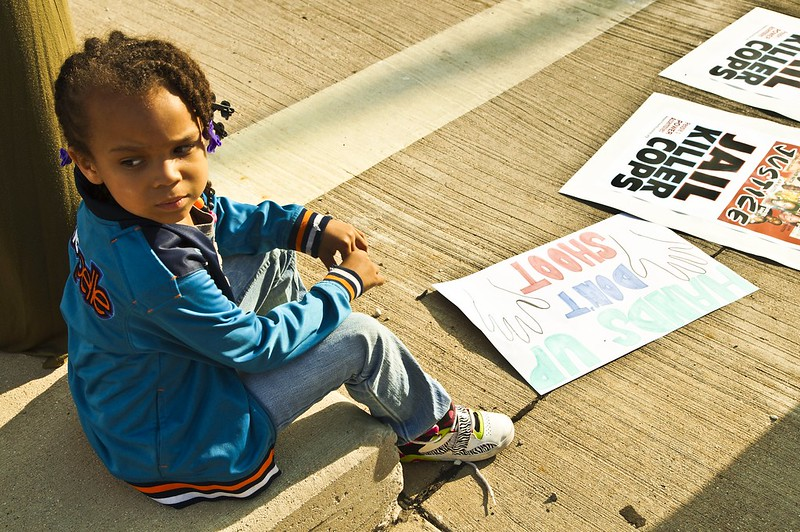 a black child sits on a curb, surrounded by protest signs