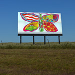 This is a Photoshop composite of 2 different images.  The background is a 9/22/13 generic billboard structure along Highway 69 in northeast Oklahoma.  I chose it because of the proportions, rural highway setting and similarity of design to vintage structures.  Then I superimposed and skewed a photocollage of an actual 21'x10' vintage 7Up UnCola paper billboard over the top.  The real paper billboard is comprised of (12) panels at 43' w x 59' high each assembled in a 'rainlap' sequence to shed water for the 30-90 days that they were pasted up.  This particular 7Up image was illustrated by Pat Dypold who illustrated the bulk of the outdoor ads (billboards) for the J. Walter Thompson [advertising] Co. of Chicago.  JWT orchestrated the entire 'UnCola' ad campaign from 1968 until the mid-seventies.  Read more about Pat in this page dedi