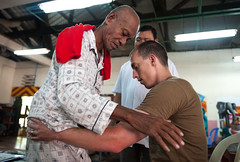 Lt. Matthew Bush assists a patient as he does walking exercises at a physical rehabilitation clinic in Phnom Penh, June 23. (U.S. Navy/MC2 Karolina A. Oseguera)