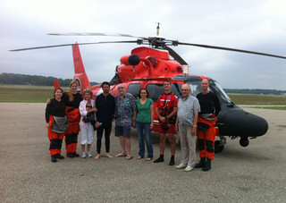 The aircrew from Coast Guard Air Facility Muskegon, Mich., stand with the man they rescued and his family at Muskegon County Airport, Sept. 1, 2014. The crew rescued the man 30 miles off-shore in Lake Michigan after he became fatigued from the adverse weather conditions and activated a personal locator beacon. (U.S Coast Guard photo courtesy of Air Facility Muskegon)
