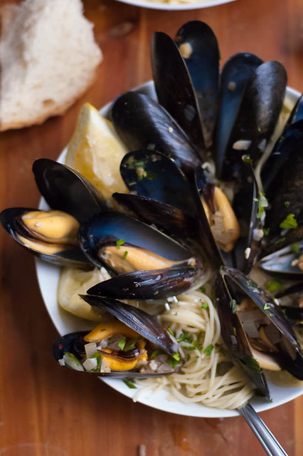 mussels in spicy white wine sauce served with pasta and crusty bread
