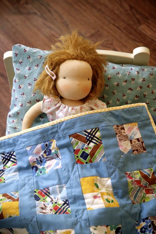Doll under her quilt.