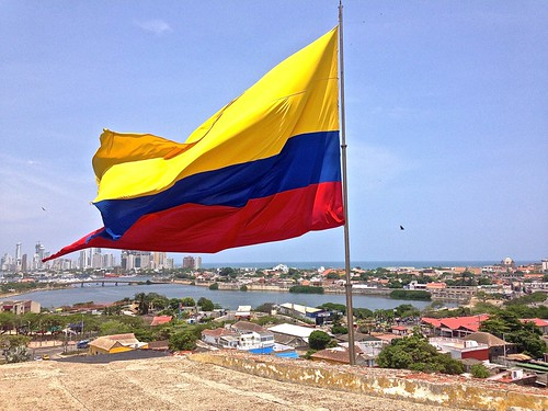 The Colombian flag waving high on Castillo San Felipe de Barajas. Cartagena's old and new cities in the distance