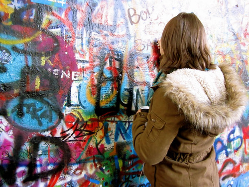 Student adds her signature to a graffiti wall on London