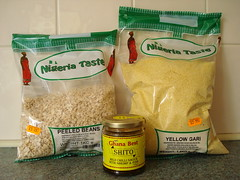 "A large clear packet marked ""peeled beans"" and another marked ""yellow gari"", both Nigeria Taste brand.  The peeled beans are small, oval, and pale brown.  In front of these is a small jar with a yellow label reading ""Ghana Best Shito / Mild chilli sauce with shrimp & fish.  They are all resting on a kitchen countertop with white tiles behind."