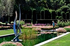backyard(0.0), swimming pool(0.0), fish pond(0.0), estate(0.0), botanical garden(1.0), shrub(1.0), flower(1.0), garden(1.0), water feature(1.0), grass(1.0), yard(1.0), green(1.0), reflecting pool(1.0), landscaping(1.0), lawn(1.0), pond(1.0),