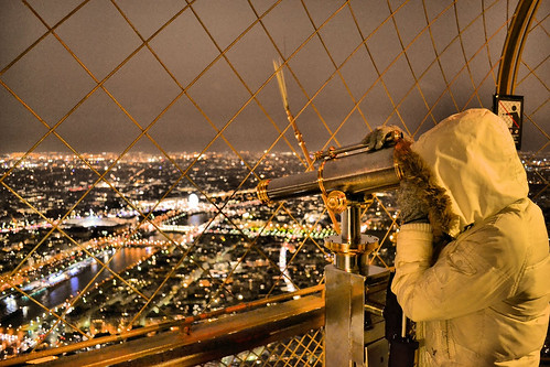 A student views the city of Paris through a viewfinder at the Eiffel Tower