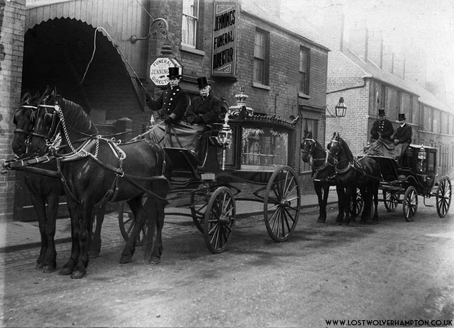 A funeral cortege arrives back at the coach house and stables on this turn-of-the-century picture.