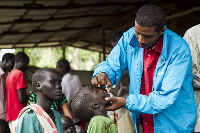 Chou San Kote watches as her son Oratine Rase as he receives polio vaccination from Lemmi Kebede, supervisor of supplementary immunisation