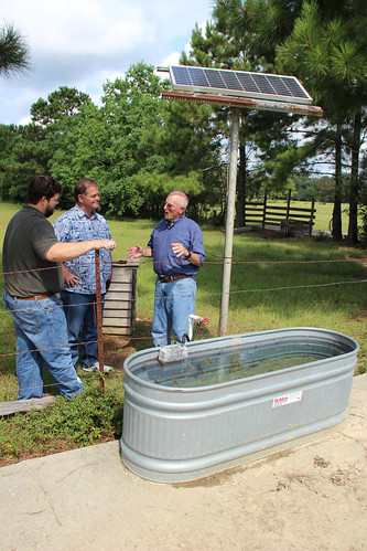 Ryan Witt, NRCS soil conservationist, Kelvin Burge, Hancock County Soil and Water Conservation District conservation technician, and Johnny Williams, Hancock County rancher, discuss the benefits of the solar powered well. NRCS photo.