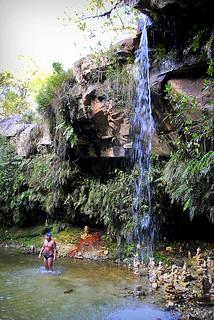 The man is enjoying a waterfall.