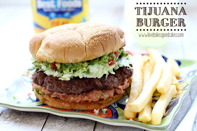Tijuana Burger on a plate with french fries.